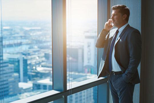Mature business CEO talking on phone alongside large high windows