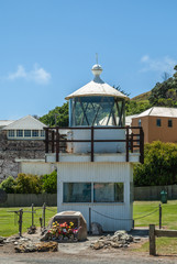 Stanley, Tasmania, Australia - December 15, 2009: Old lighthouse display consisting of wooden understructure and metal circular top under blue sky with green hills and housing in back. Memorial with f