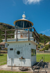 Stanley, Tasmania, Australia - December 15, 2009: Closeup of old lighthouse display consisting of wooden understructure and metal circular top under blue sky with green hills and housing in back.