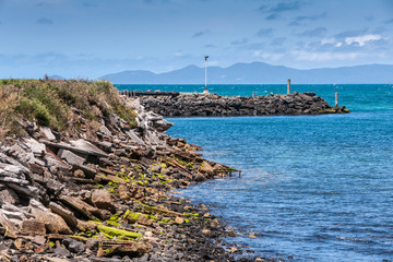Stanley, Tasmania, Australia - December 15, 2009: Rocky coastline and breakwater of the port in blue seawater under blue cloudscape with dark hills on other side of bay.