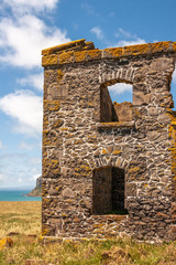 Stanley, Tasmania, Australia - December 15, 2009: Hightfield Historic Site. Wall with 2 window holes in gray stone building ruins against blue sky with white clouds.