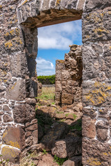 Stanley, Tasmania, Australia - December 15, 2009: Hightfield Historic Site. Looking through window hole of gray stone building ruins against blue sky with white clouds.