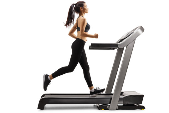 Full length profile shot of a young slender woman running on a treadmill isolated on white background