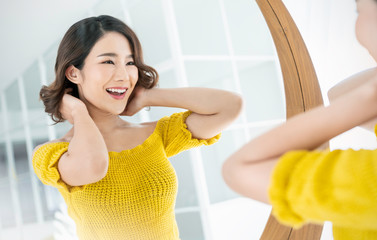 Closeup portrait of young beautiful asian girl  with mirror for makeup routine with copy space. Beauty woman with perfect glow skin dress up in yellow. Health care woman lifestyle cosmetic concept