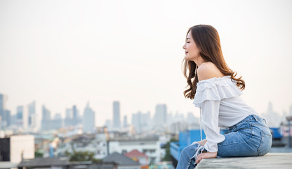 Portrait of young beautiful asian woman sitting in sky fresh air roof top. Smile face asian girl wear casual. Beauty treatment perfect clear skin japanese makeup asia woman lifestyle concept