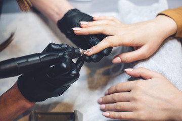 Foto op Plexiglas Manicure Beautician Salon, Manicure, Nails Polish Procedure. Professional hardware manicure using electric machine in beauty salon. master uses an electric machine to remove nail polish hands during manicure