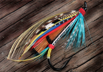 A closeup pic of a colourful fly fishing lure on a rough wooden surface