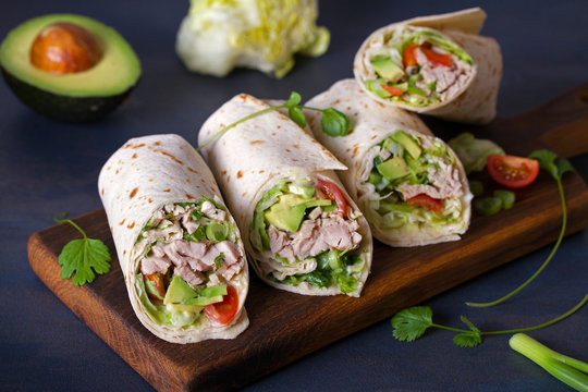 Turkey wraps with avocado, tomatoes and iceberg lettuce on chopping board. Tortilla, burritos, sandwiches, twisted rolls