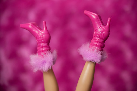 WOODBRIDGE, NEW JERSEY - May 10, 2019: A Barbie Doll does a handstand to show off her pink high-heeled boots with furry cuffs