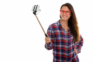 Happy young beautiful hipster woman taking selfie with phone on selfie stick