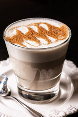 A cup of Chai Latte on a white saucer against a dark background