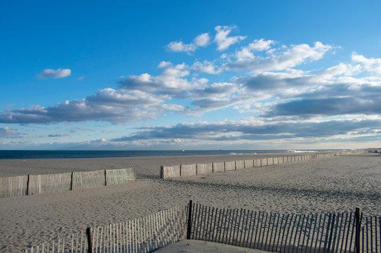 Heavy surf crashing into a sandy shoreline at Belmar Beach, New Jersey, USA, under a partly cloudy sky
