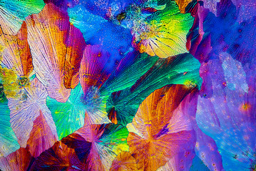 Extreme macro photograph of Paracetamol crystals forming abstract modern art patterns, when illuminated with polarized light, under a microscope objective with 50x magnification