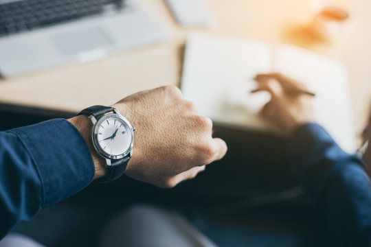 looking at luxury watch on hand check the time at workplace.concept for managing time organization working,punctuality,appointment.fashionable wearing stylish