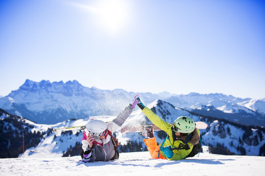two girls with ski and snowboard having fun on snow