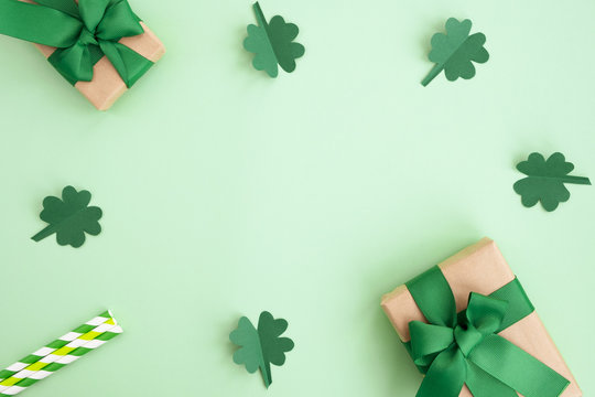 St Patrick's Day composition. Gift boxes, clover and festive decor on a light green background. Top view, flat lay, copy space