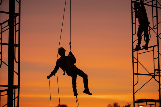 Silhouette Construction site Engineers are abseiling with a zip line.