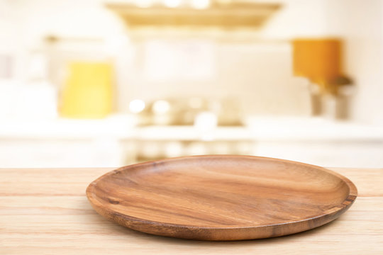 Empty wooden tray on perspective wooden table on top over blur flower background. Can be used mock up for montage products display or design layout.