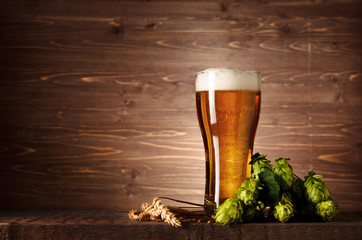 Foto auf Leinwand Alkohol Beautiful tasty beer with foam in glass glass with hops cones and wheat ears on dark wooden table background with copy space