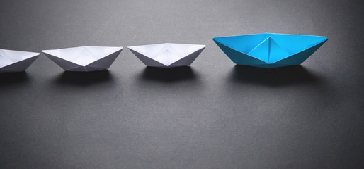 Blue and white paper boat. Leadership concept