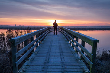 A man on a wooden bridge over a lake enjoying the view during a tranquil sunrise.