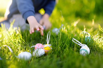 Little boy hunting for easter egg in spring garden on Easter day. Focus on multicolor eggs.