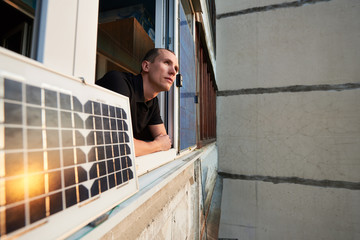Young man on balcony of residential building with solar panel in which the sun is reflected at sunset. Concept converting solar radiation into electricity