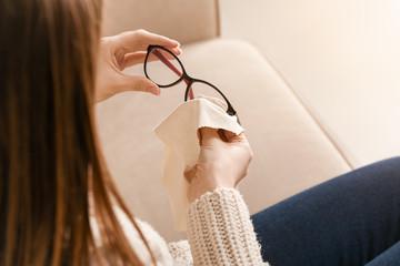Young woman wiping eyeglasses at home, closeup