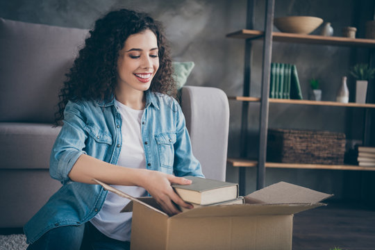 Portrait of her she nice attractive lovely cheerful cheery wavy-haired girl packing own things library moving in modern loft industrial style interior living-room indoors
