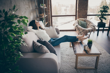 Profille side view portrait of her she nice attractive charming cheerful cheery glad wavy-haired girl sitting on divan resting spending day at modern industrial loft interior style living-room indoors