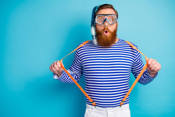 Portrait of astonished redhair man train watersport swim coral reef pull his modern suspenders wear...
