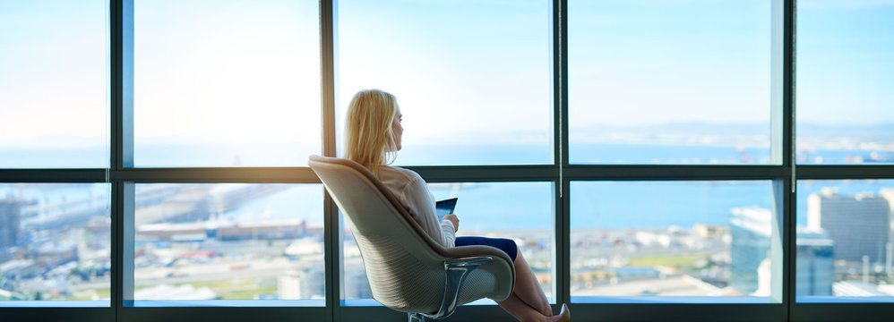 Businesswoman sitting in an office looking out at the city