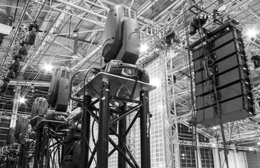 Moving head spotlight devices on a truss. Line array speakers. Installation of professional stage, sound and light equipment for a concert. Fotoväggar