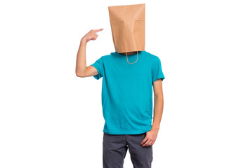 Fototapete - Portrait of teen boy pointing finger at paper bag over head, isolated on white background. Child posing in studio.