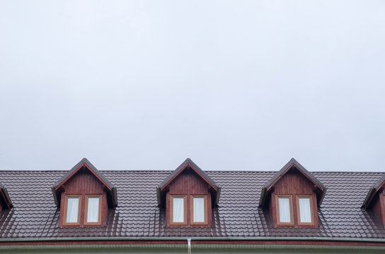 Three wooden dormers with windows on new brown metal roof.