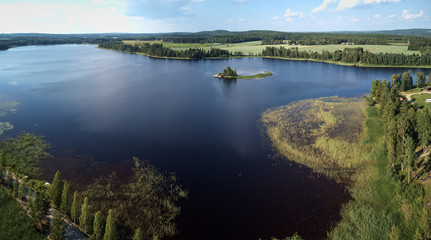 Aerial view of blue lake and green forests on a sunny summer day. Bird's eye view drone photography. Ruovesi, Finland.
