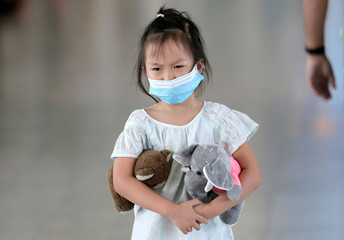 A girl wears a mask as she walks past a scanning machine monitoring people's temperature following the new coronavirus outbreak from China, at Bandaranaike international airport in Katunayake