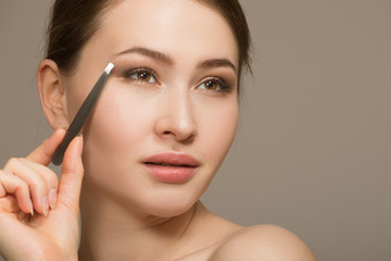 Eyebrow correction. Closeup of a beautiful young woman. plucking eyebrows. Portrait with tweezers near the eyebrows. Beauty concept.