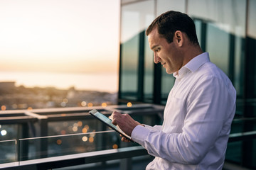 Smiling businessman standing on an office balcony using a tablet Wall mural