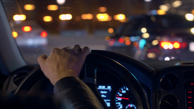 Man's hands on the steering wheel. Night driving