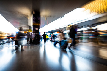 people in the station as they walk fast, blurred photo