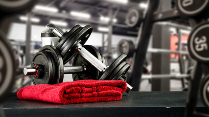 Poster Fitness Black desk of free space for your decoration and blurred gym interior.Metal dumbbells and fit life
