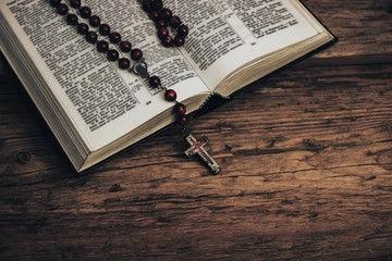 Top view Open Holy Bible and beads crucifix on a old oak wooden table. Beautiful red wall background.
