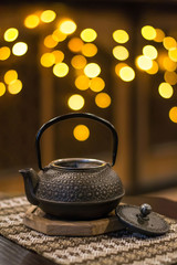 Still life with traditional vintage asian cast iron kettle with open cap on background with warm yellow bokeh lights. Woven tablecloth with textured national pattern.