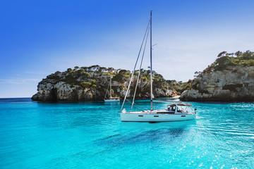 Beautiful beach with sailing boat yacht, Cala Macarelleta, Menorca island, Spain. Yachting, travel...