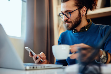 Young handsome bearded hipster sitting at his home office, holding cup of coffee and using smart phone.