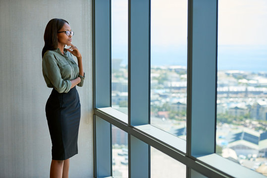 Young executive deep in thought looking through office tower windows