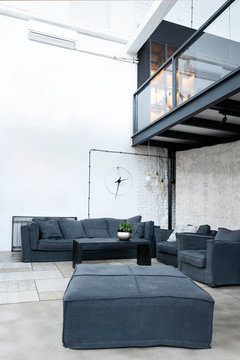 Interior of living room in loft apartment in industrial style. Modern grey furniture, design sofa and white brick wall. Minimal and simple scandinavian indoors. Vertical.