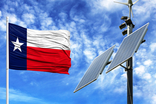 Solar panels on a background of blue sky with a flagpole and the flag State of Texas