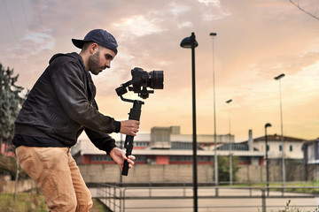 Caucasian videographer filming with cinema gimbal video dslr at sunset , professional video, videographer in event. Cinema lens on gimbal. Medium shot from right side